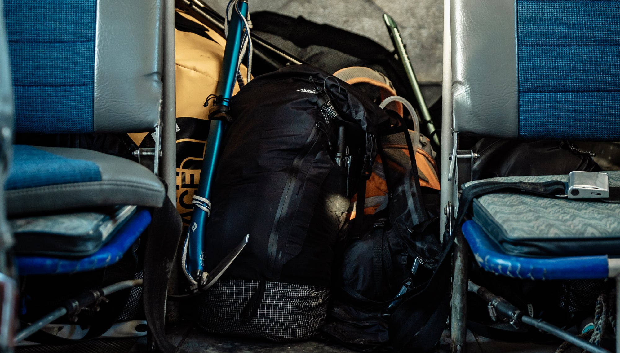 Backpack in a pile of gear between plane seats