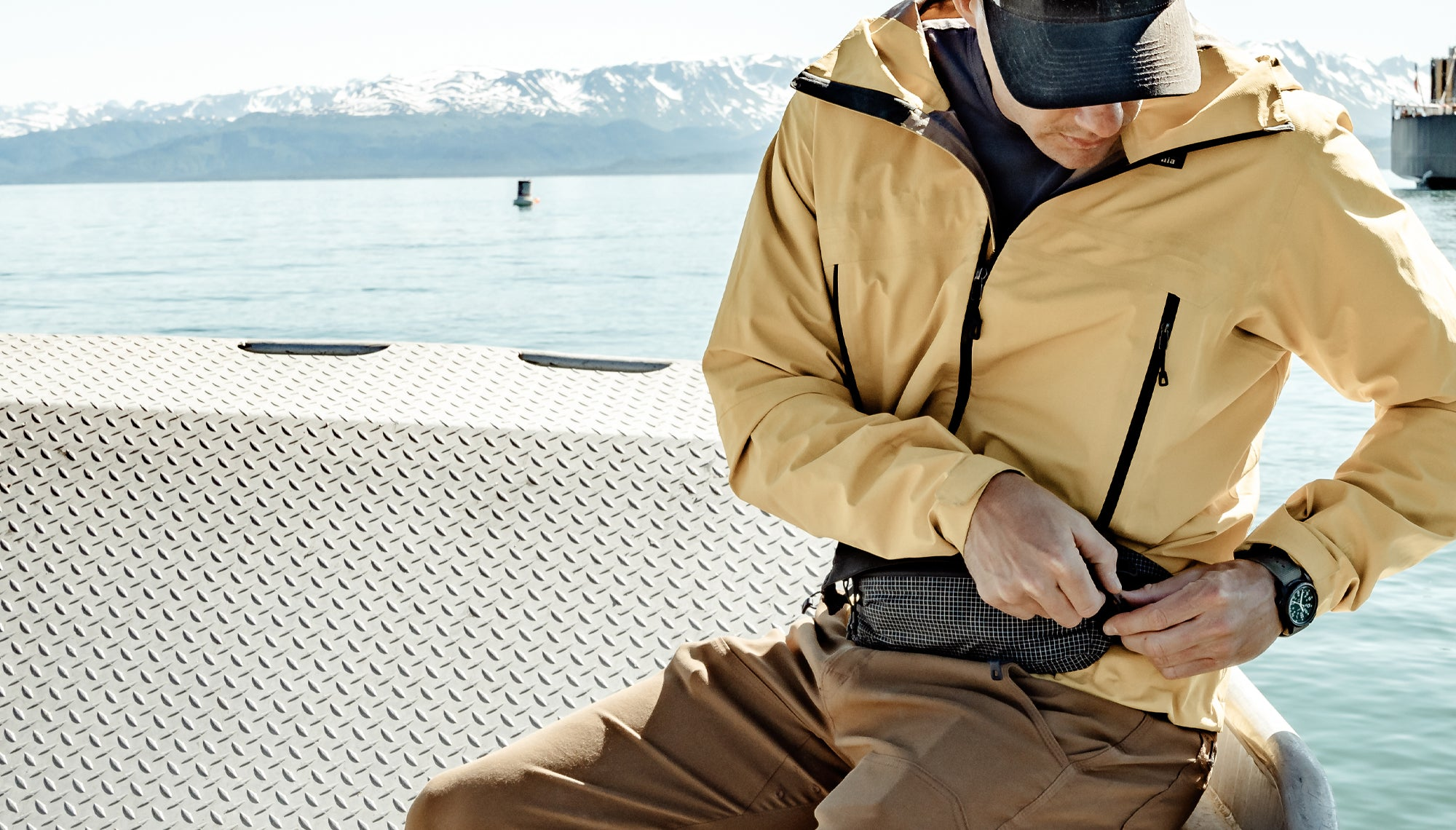 Man in boat, zipping up hip pack