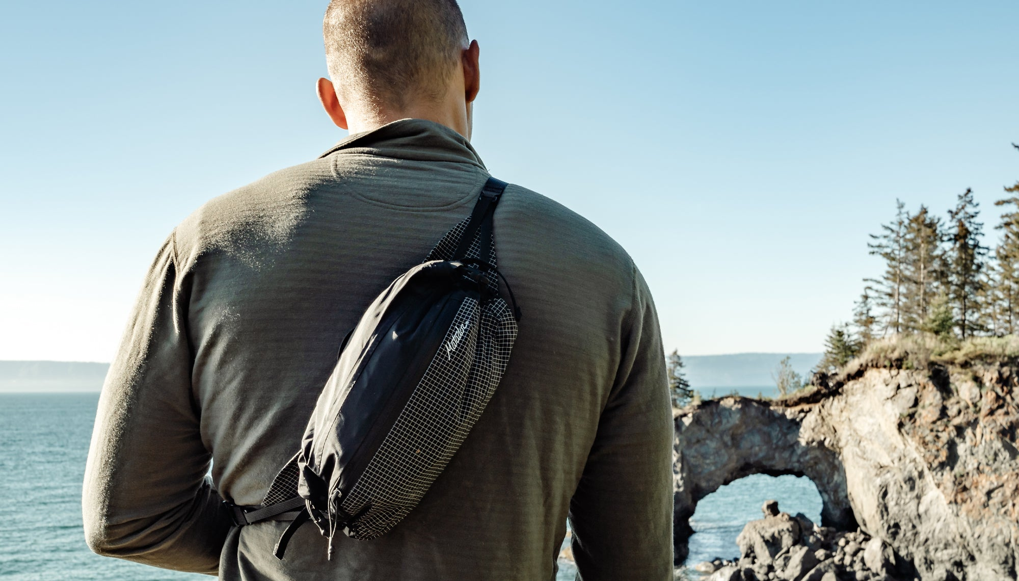 Man looking out at ocean wearing crossbody hip pack
