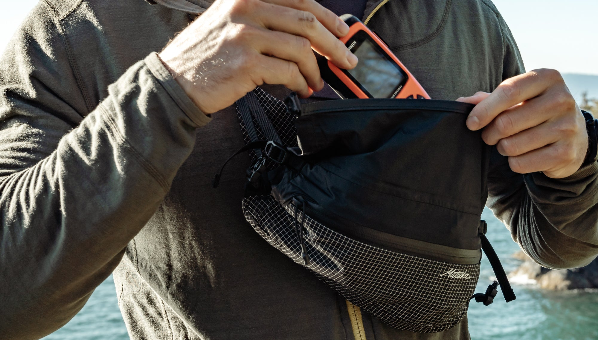 Man placing GPS device into cross body hip pack