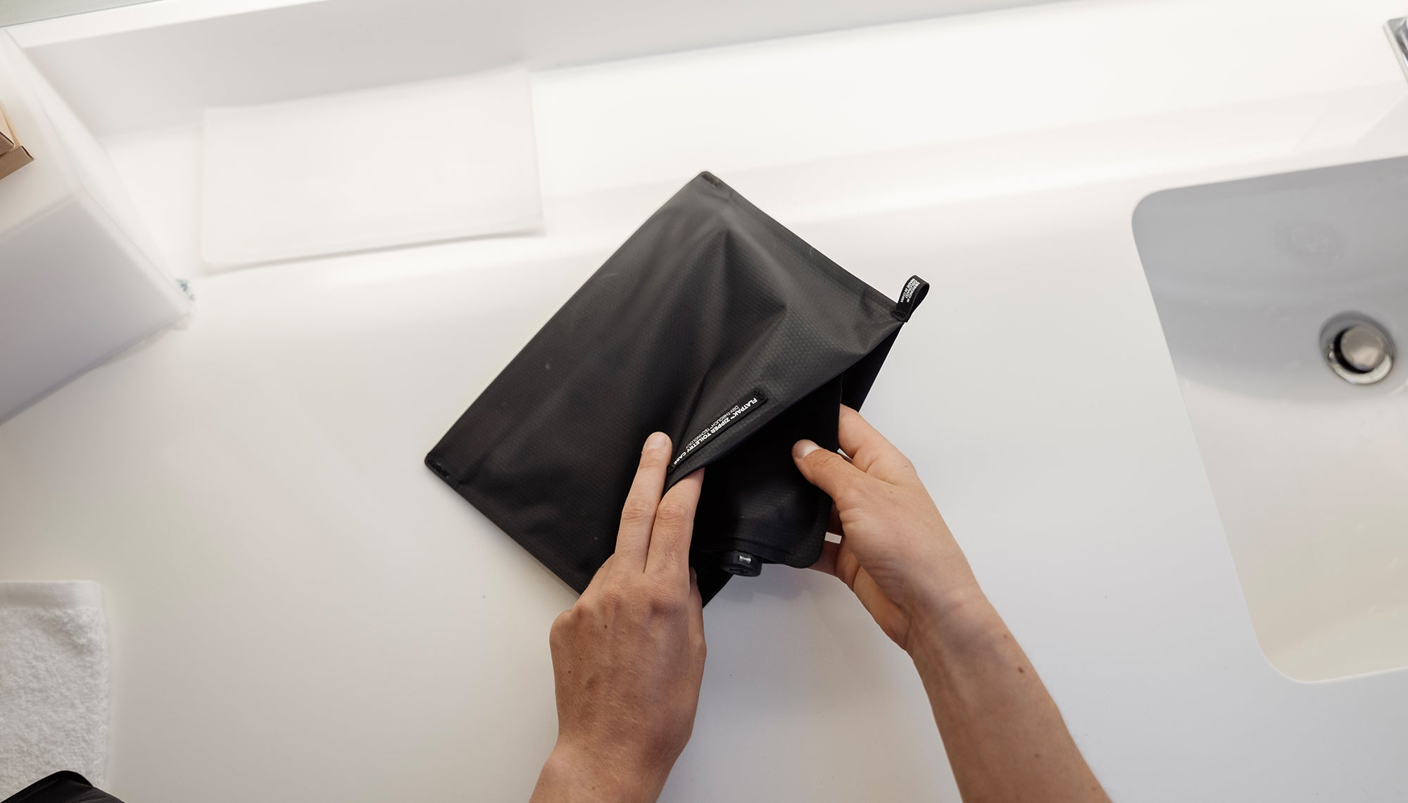 Hands pulling flatpak toiletry bottle from zipper case on bathroom counter