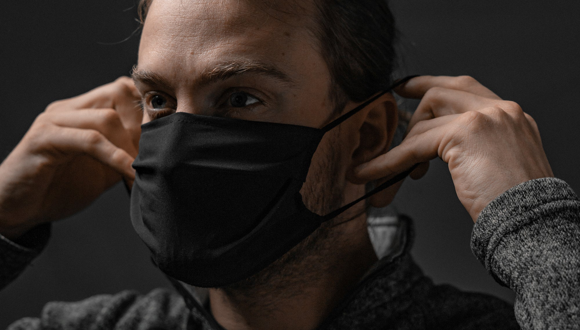 Front view of man placing facemask on face