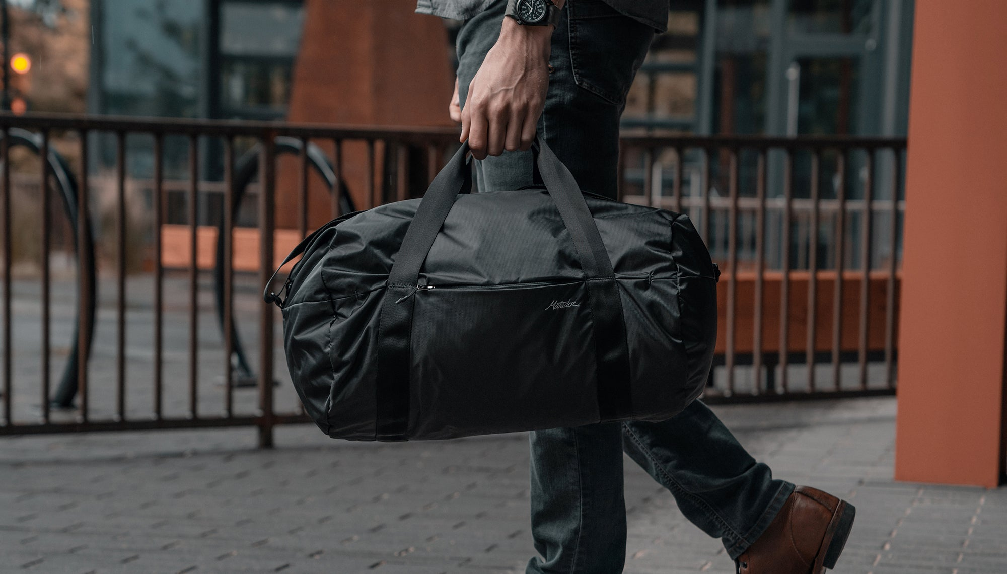 Man in city, carrying duffle by carry handles