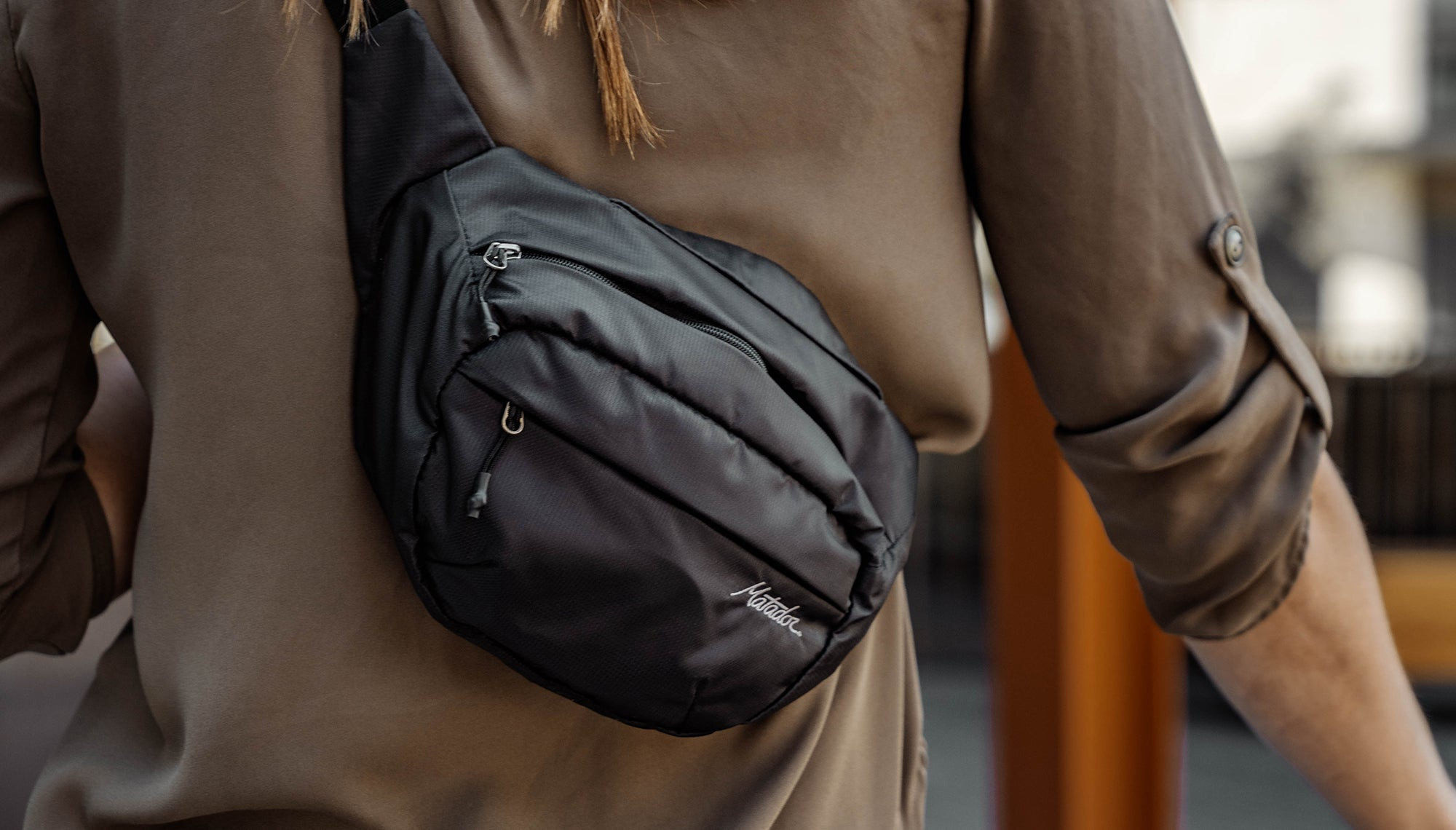 Woman in city, wearing hip pack across her back