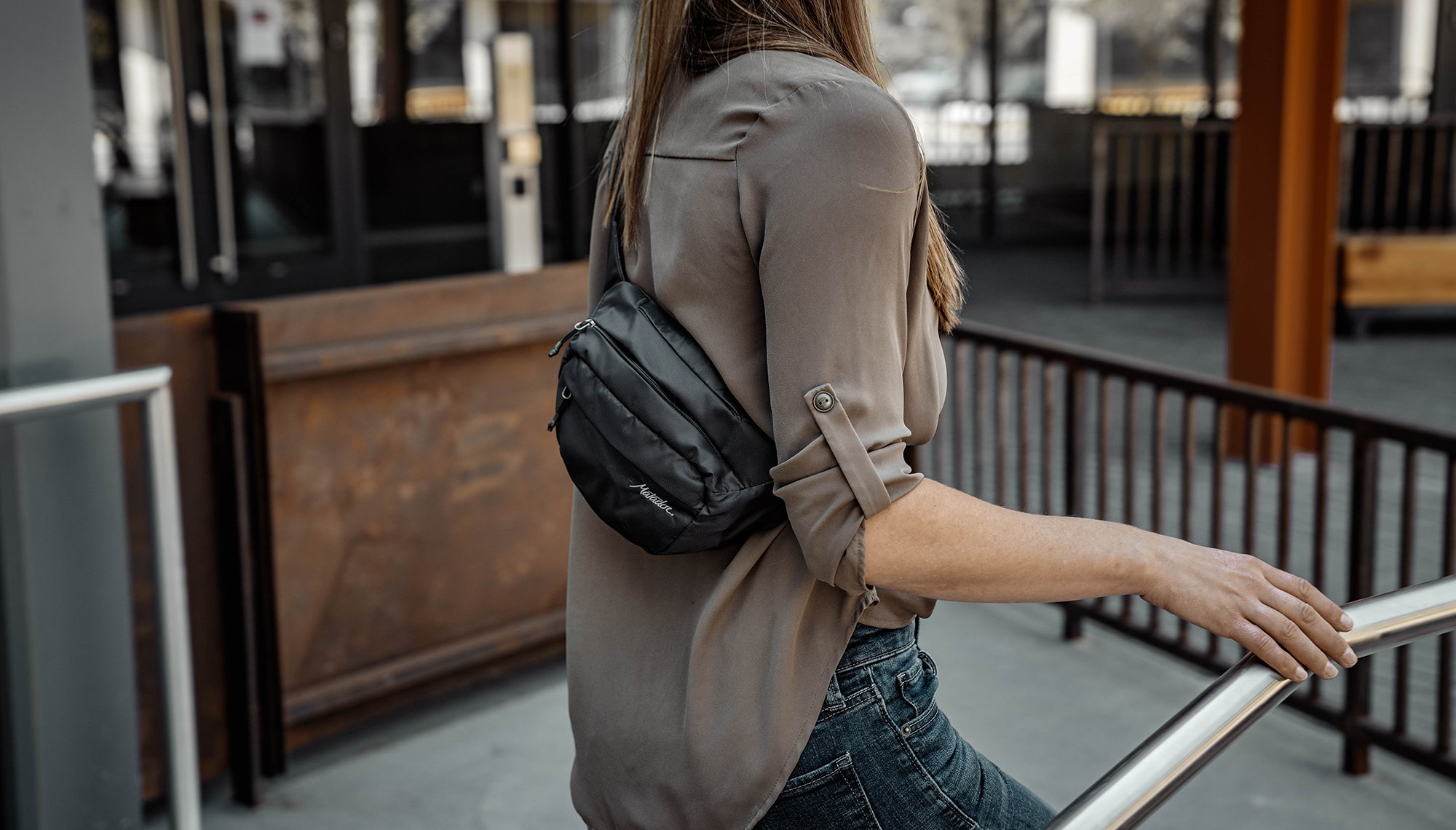 Woman walking in city with hip pack across her back