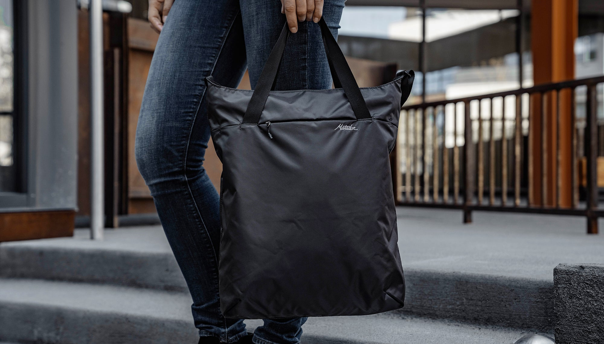 Woman in city, carrying tote by carry handles