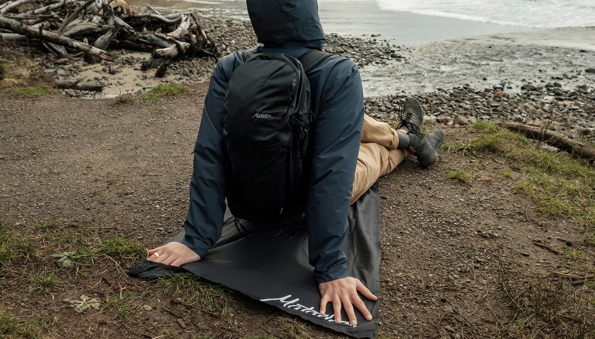 Man looking out at beach, sitting on pocket blanket