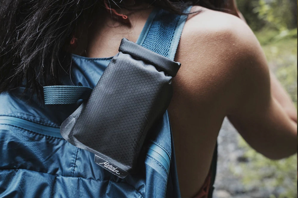 Flatpak clipped to shoulder strap of woman's backpack