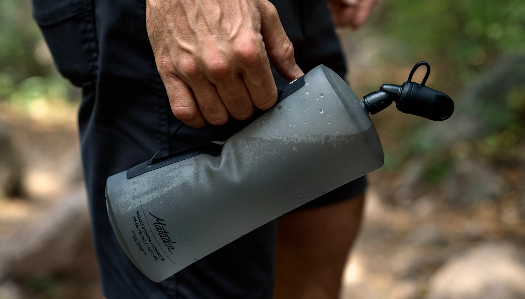 Man hiking, holding full water bottle from carry handle