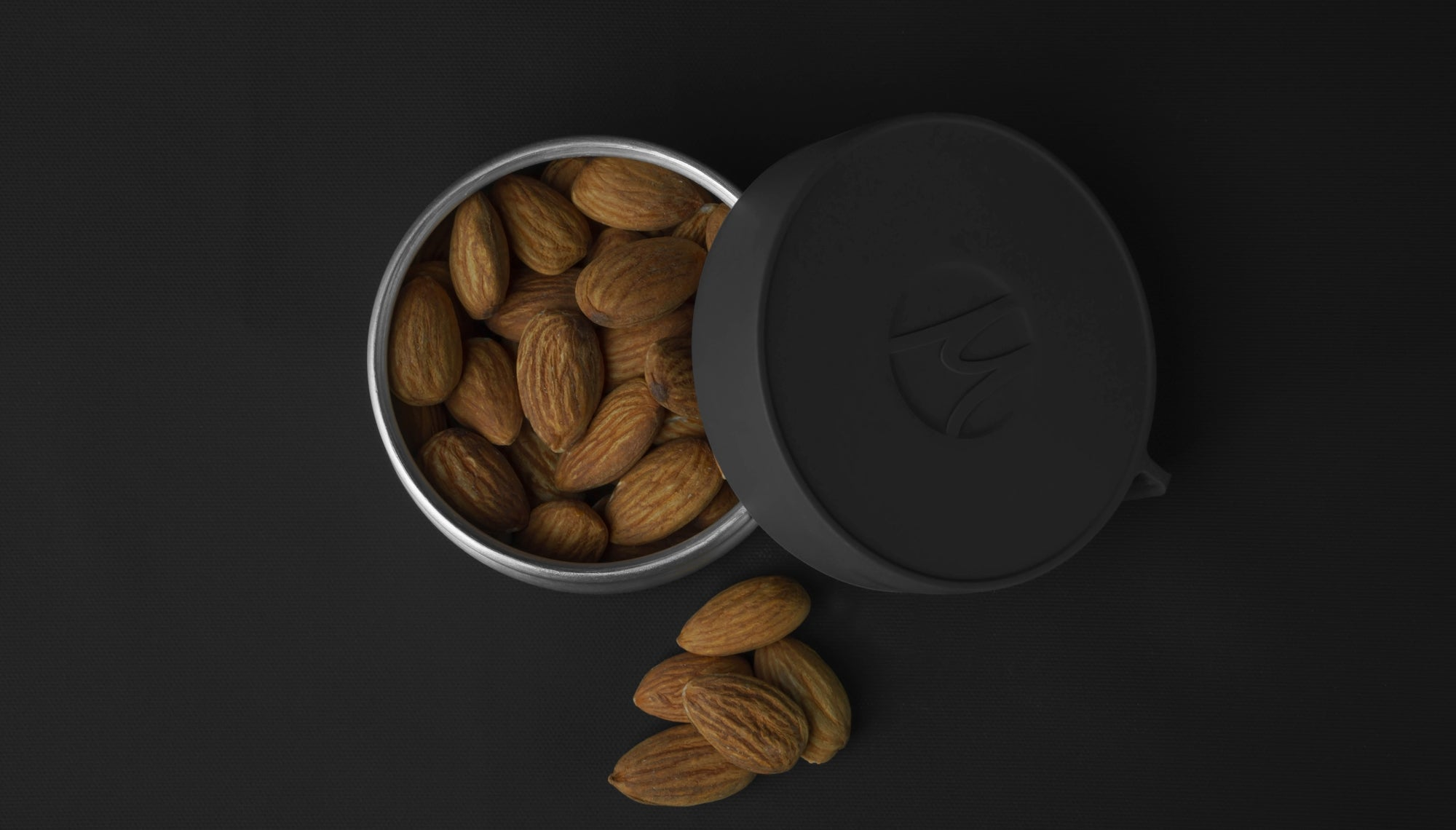 Top view of canister on black background filled with almonds