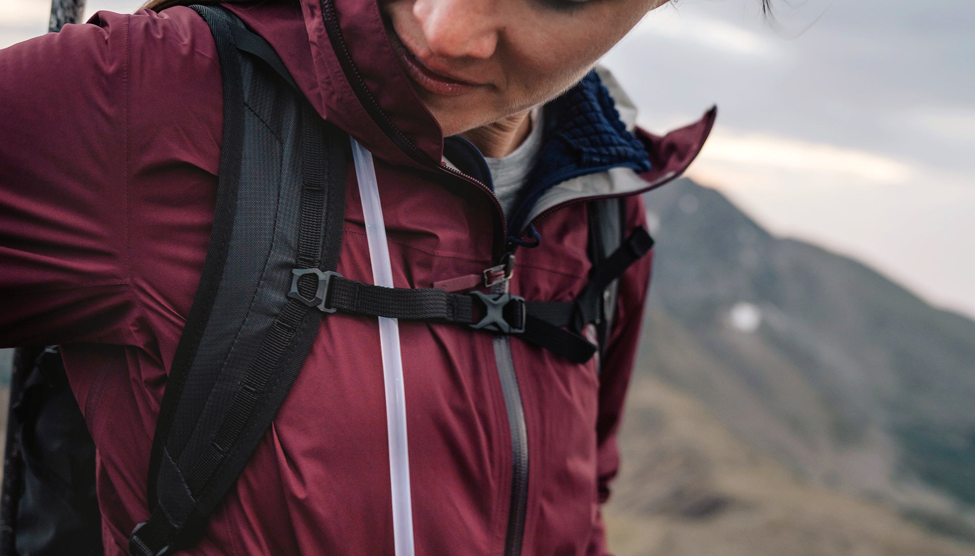Woman in headlamp looking at backpack straps