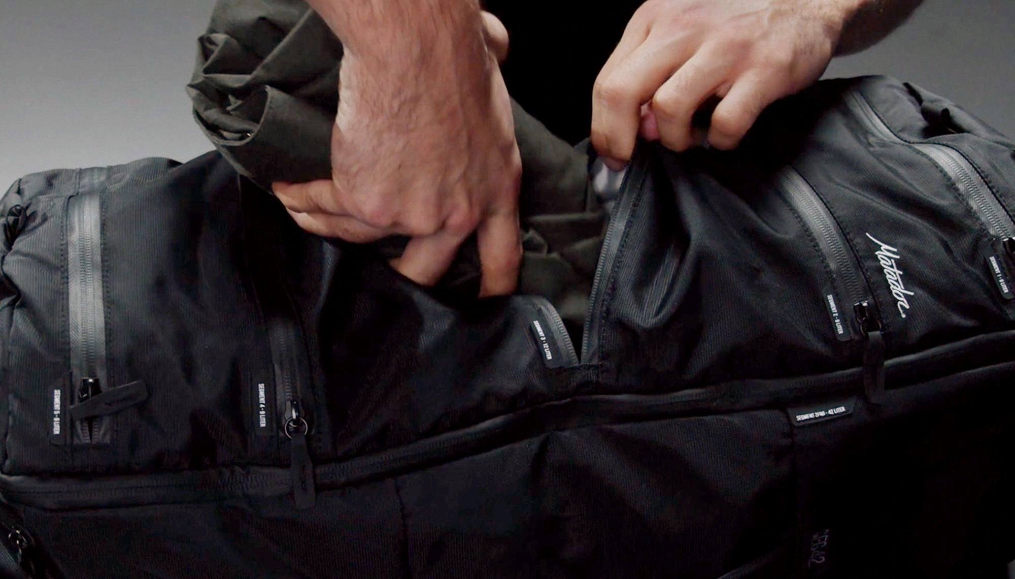 Man stuffing clothing into zipper compartment