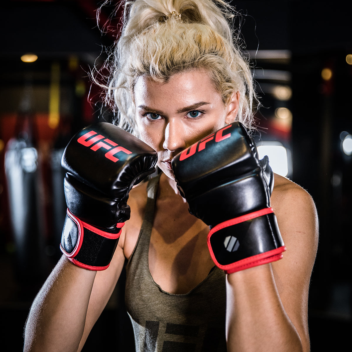 Athlete wearing and holding the gloves in front of her face