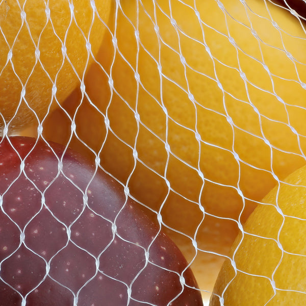 "Close-up of Apples and Oranges in 24"" Clear Plastic Mesh Bag"