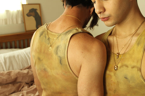 Two men facing each other wearing tank tops and gold jewelry