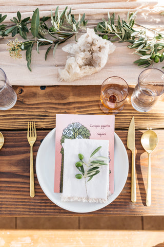 Curated dinner table with flowers, menu and place setting against wooden table