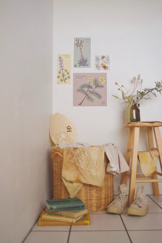 Bedroom with wicker hamper with shirts, stool and botanical prints hanging on the wall