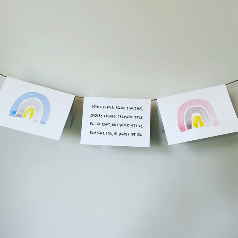 What to say when someone has a miscarriage - 3 miscarriage cards, one with blue and yellow rainbow, displayed on length of string, one with pink and yellow rainbow and one with miscarriage remembrance verse.