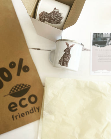 Image of our packing table - featuring a hare enamel mug, an otter enamel mug, our compostable mailer, recyclable tissue paper and a thank you for your order postcard.