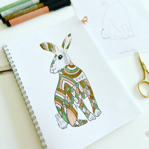 Image of desk with notebook featuring a rabbit colouring in page, with gold scissors and colouring pens beside and above the notebook