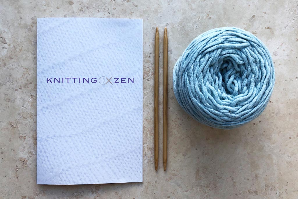 Guidebook, knitting needles and a ball of yarn on a marble surface