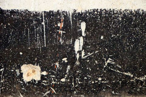 Dried and cracking tar along the concrete wall of a foundation, where a basement is being damp proofed