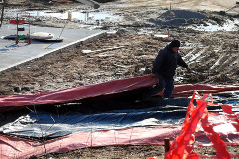 A foreman lugging a large concrete blanket away from a work site after the concrete has cured.