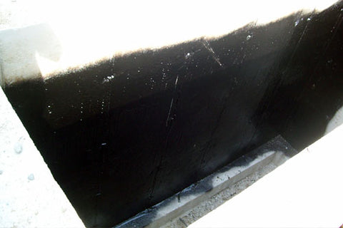 Freshly applied tar on a foundation in new construction, and not yet cured.