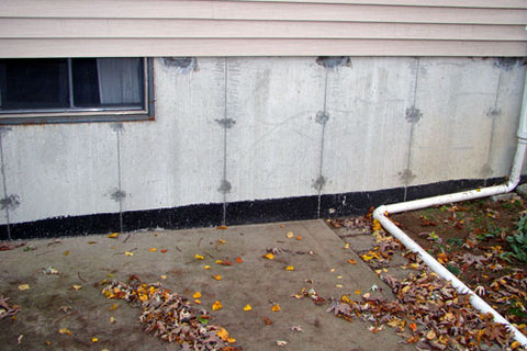 A view along the foundation of a house, where grade line tar was applied above the grade.  A black line of tar is visible on the concrete.