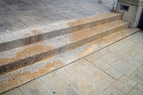 Pavers stained by water runoff that has seeped into the pores of the concrete surface