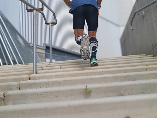 showing a man from waist down running in the heat up the stairs in Penguin Dojo knee high running socks