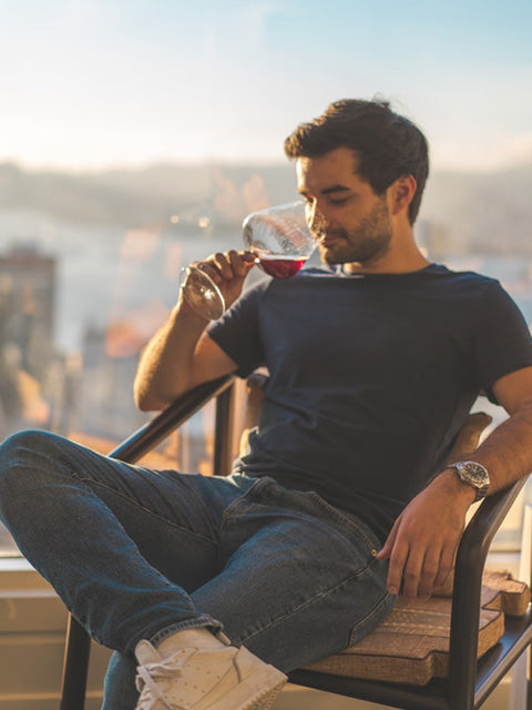 man sitting in a chair relaxing and drinking wine