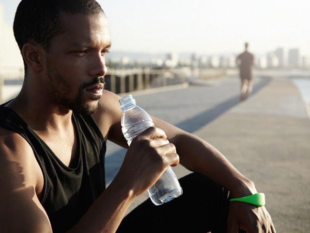 sportsman sitting on a pavement drinking water looking into distance exhausted from the heat