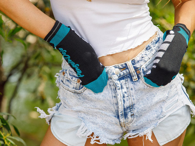 woman wearing white t-shirt and shorts and Penguin Dojo no-show socks on her hands