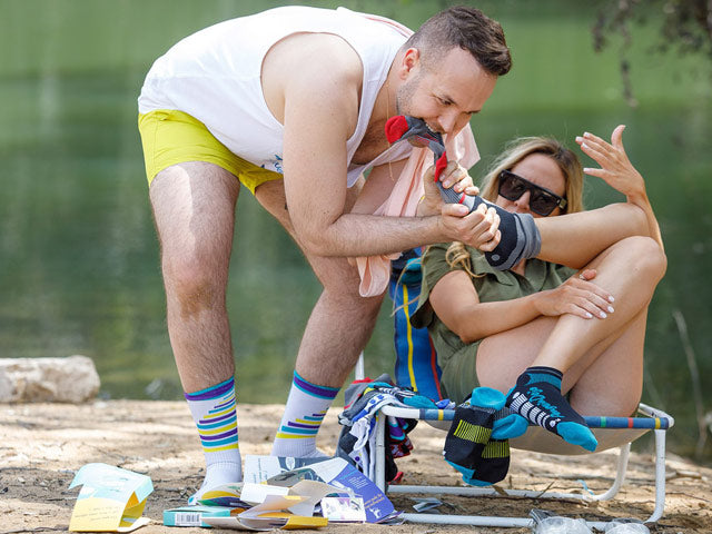 a man and a woman goofing around with no show socks by the lake