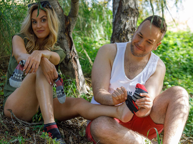 a man taking a sock off woman's feet smiling