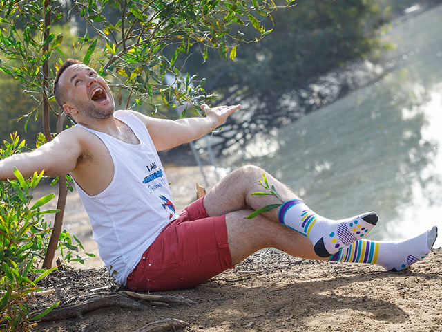 man sitting on the ground by the lake with extended arms and happy face in Penguin Dojo Jockey crew socks for sweaty feet