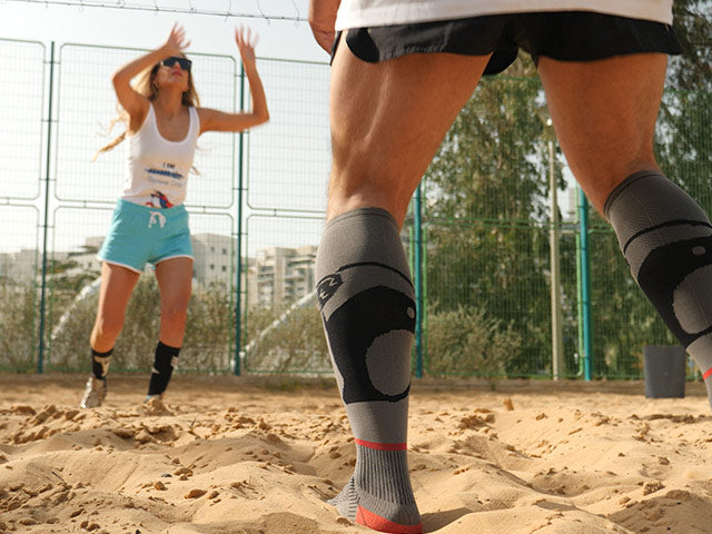 a man and a woman playing volleyball in shorts and knee high running socks