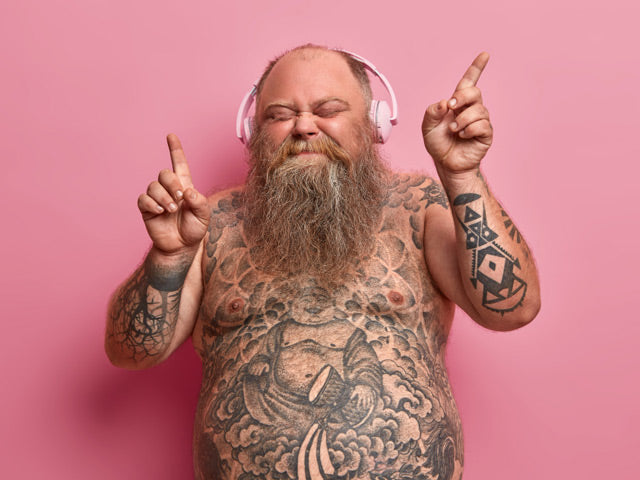 naked fat man with tattoos listening to the music and dancing