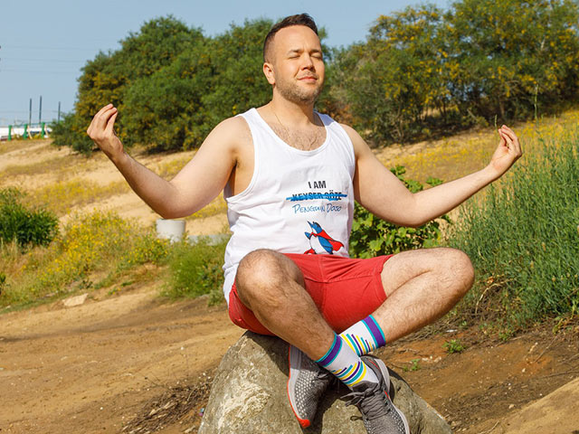 man in exercising gear sitting on a rock meditating