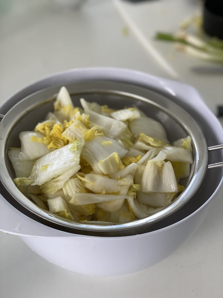 napa cabbage being drained after rinsing off salt brine