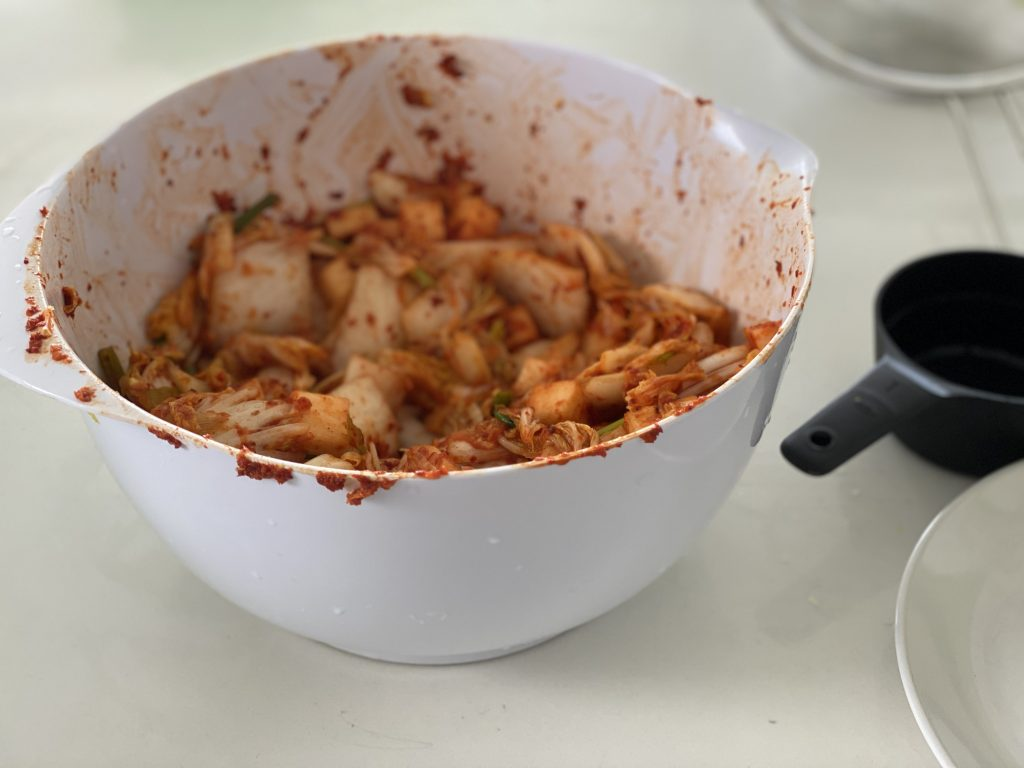 napa cabbage and other veggies mixed together with chili paste ready to be stored in jars.