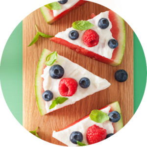 Tasty and refreshing slices of watermelon pizza topped with fresh fruit and yogurt are plated on a wooden slab.