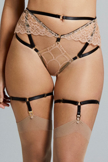 Close up view of Colette bondage-inspired garters are an alternative to a traditional suspender belt. Created to hold up your stockings and complete any Edge o' Beyond underwear look. Finished with 24 carat gold hardware to match our gold jewellery. The perfect add on to lingerie shopping.