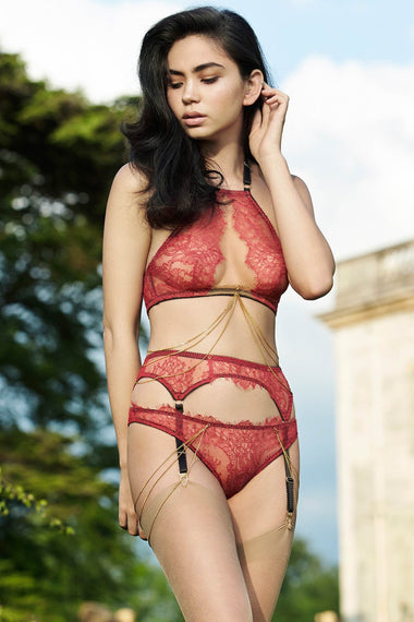 The Edge o' Beyond Elise peep bra crafted from red rouge French Chantilly lace + luxury 24 carat gold plated details. Cups add push up and support. Bondage inspired adjustable back and halter neck mean a good plus size lingerie or underwear option. Image includes 18k gold plated jewellery and suspender belt and brief