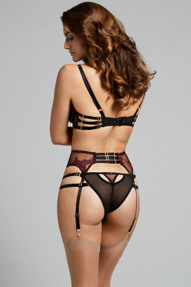 Fabienne features corded French Lace in rich mulberry. Finished with adjustable, bondage-inspired silky straps and gold dipped rings the underwired, lace covered, three piece push up bra is the ultimate lingerie piece. Back view of plus size lingerie model with suspenders and brief