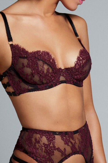 Fabienne features corded French Lace in rich mulberry. Finished with adjustable, bondage-inspired silky straps and gold dipped rings the underwired, lace covered, three piece push up bra is the ultimate lingerie piece. Shown with suspender belt