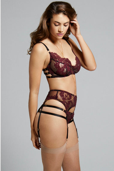 Fabienne features corded French Lace in rich mulberry. Finished with adjustable, bondage-inspired silky straps and gold dipped rings the underwired, lace covered, three piece push up bra is the ultimate lingerie piece. Shown on plus size lingerie model with suspenders and thong