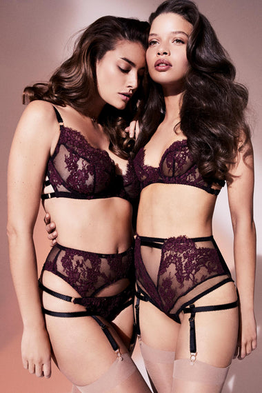 Fabienne features corded French Lace in rich mulberry. Finished with adjustable, bondage-inspired silky straps and gold dipped rings the underwired, lace covered, three piece push up bra is the ultimate lingerie piece. Shown as full set on two models with high waist, suspenders, thong