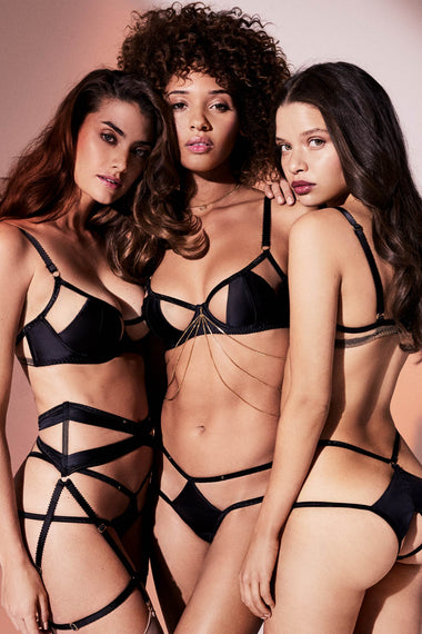Edge o' Beyond Madeleine suspender is made from black silk and 18 carat gold dipped rings. This women's lingerie garter belt is almost corset like as it draws in the waist.  Shown as full lingerie set across three models, one plus size lingerie model